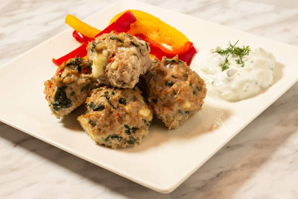 Greek meatballs on a plate with tzatziki and sauteed peppers.