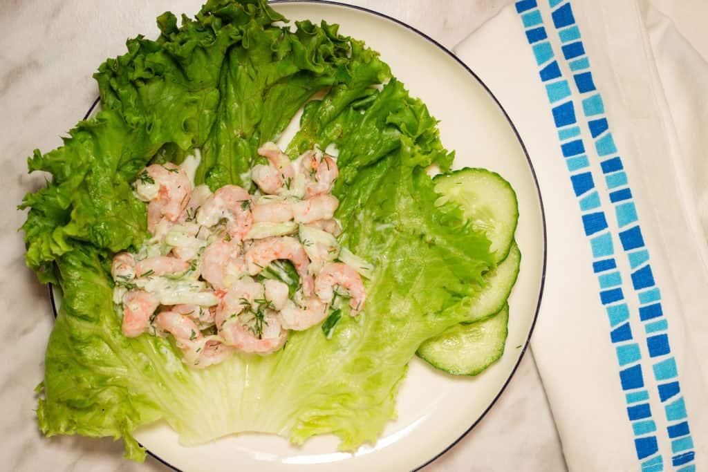 Keto shrimp salad with cucumber on a leaf of lettuce.