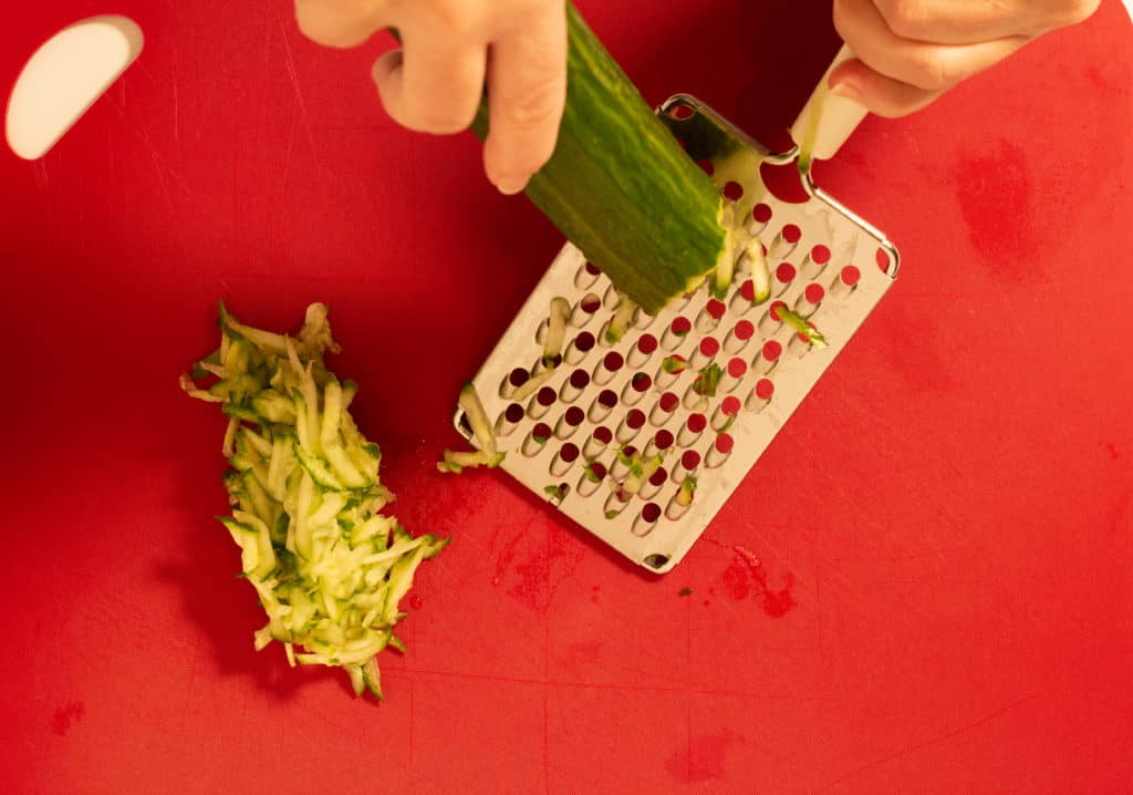 Grating an English cucumber with a cheese grater.