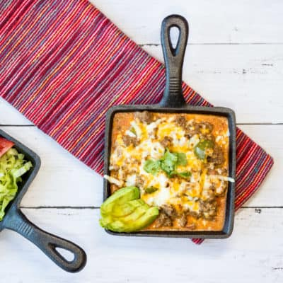 Tex-Mex Beef Casserole in a small square cast iron serving dish with another dish of lettuce and tomato on the side.
