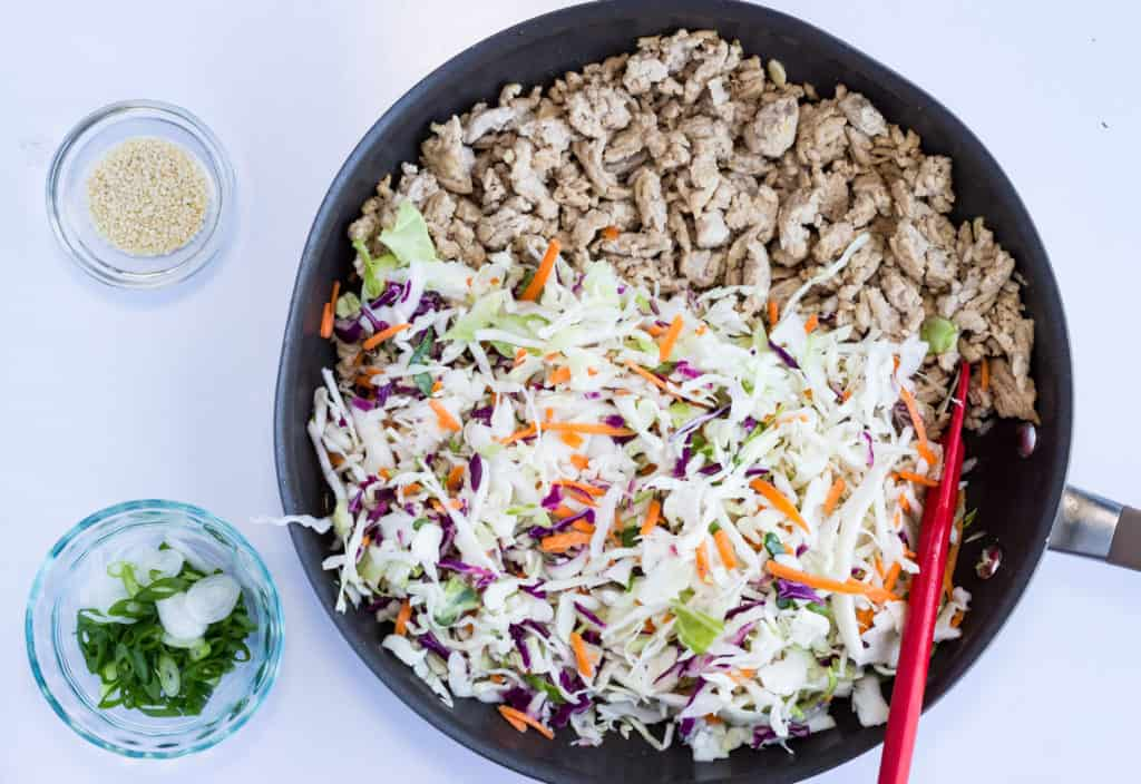 Keto Egg Roll in a Bowl cabbage and cooked pork in a skillet