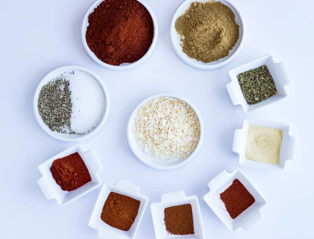 A rainbow of ingredients in small dishes to make keto taco seasoning.