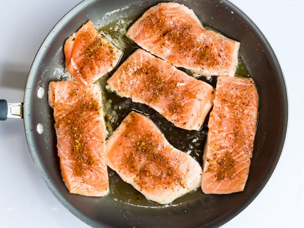 salmon fillets in pan seasoned