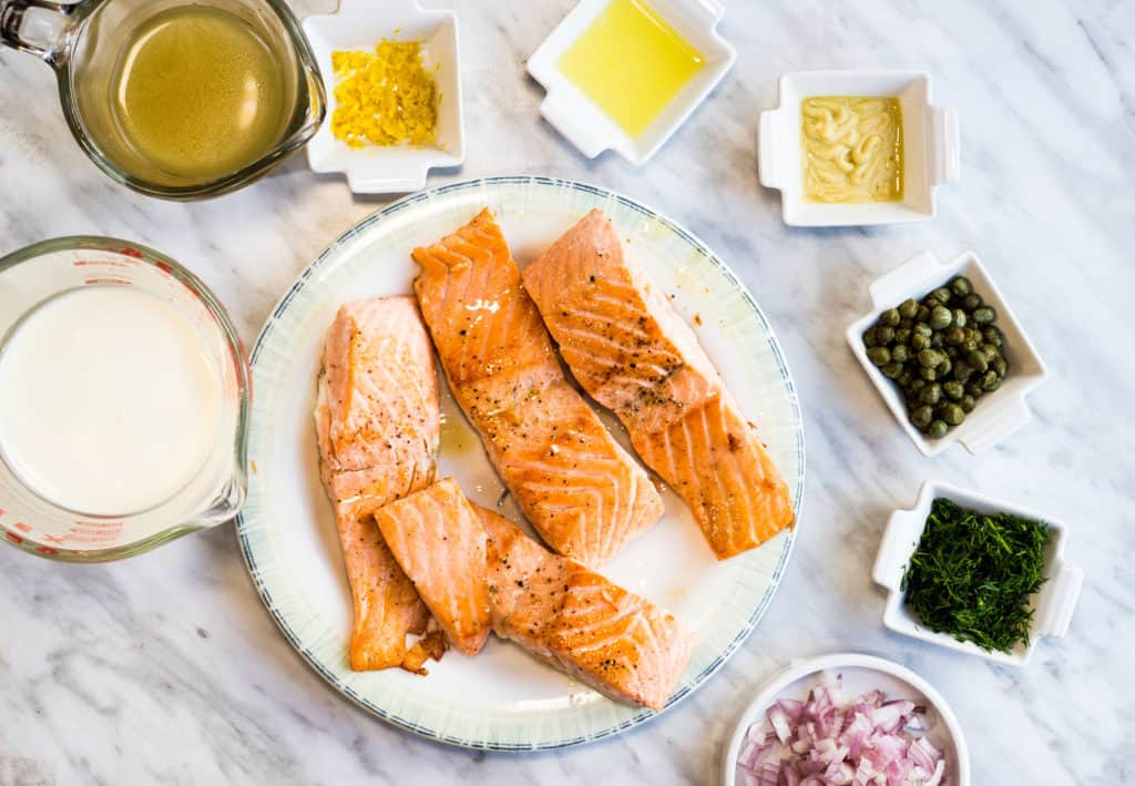 cooked salmon and prepped ingredients to make keto salmon with lemon dill cream sauce