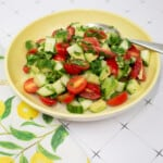 cucumber, tomato, avocado salad in a serving bowl with a napkin and spoon