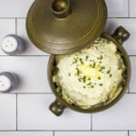 cheesy cauliflower mash in a casserole dish with the lid